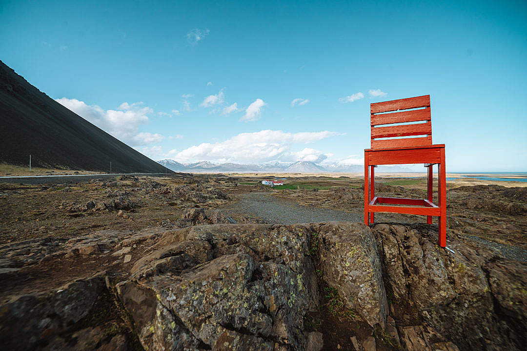 Download A Giant Red Chair Bolted to a Rock in Iceland FREE Stock Photo