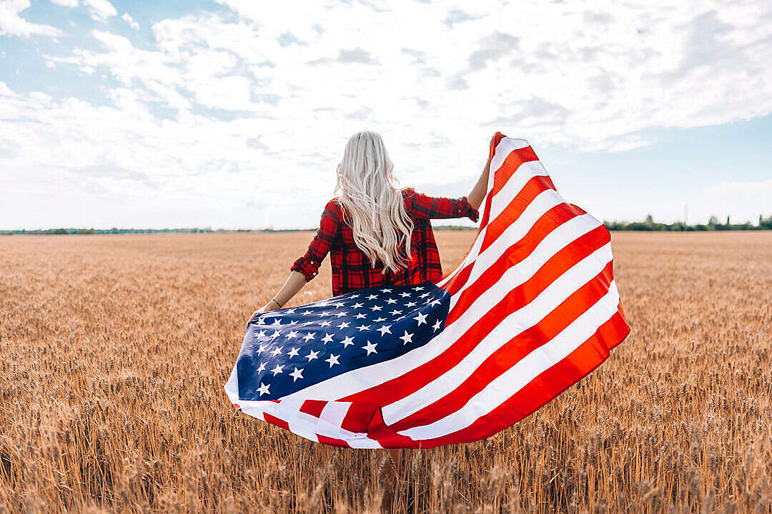 Download A Woman Walking in a Field with The American Flag FREE Stock Photo