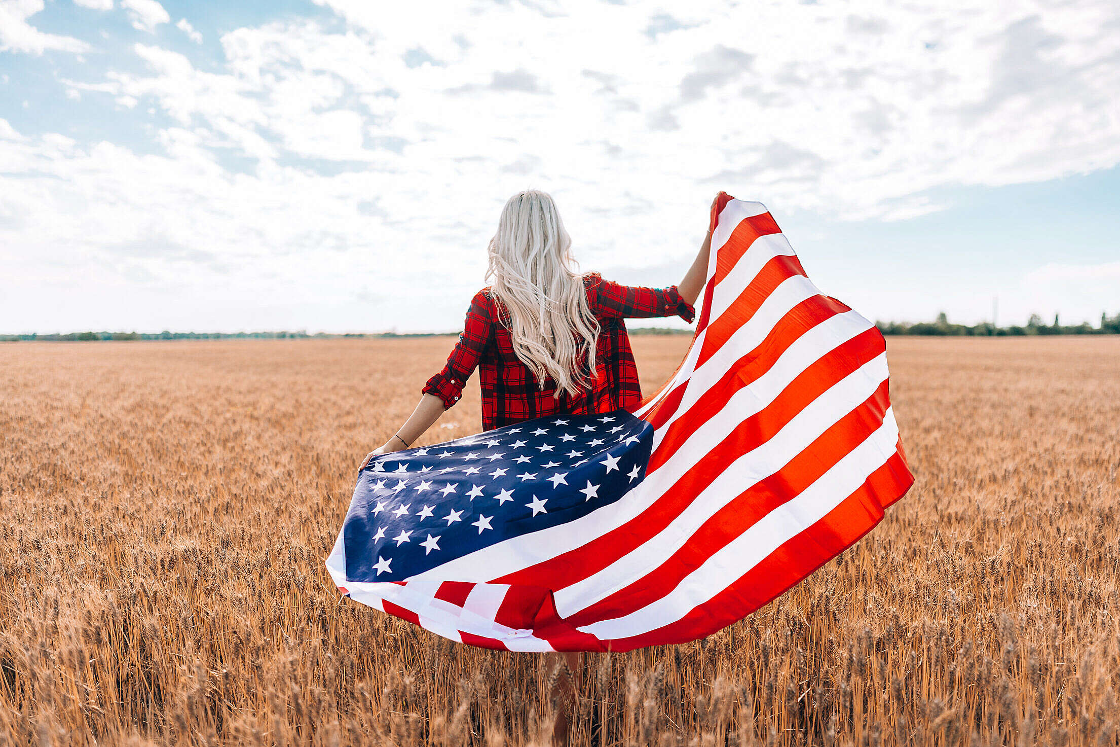 A Woman Walking in a Field with The American Flag Free Stock Photo
