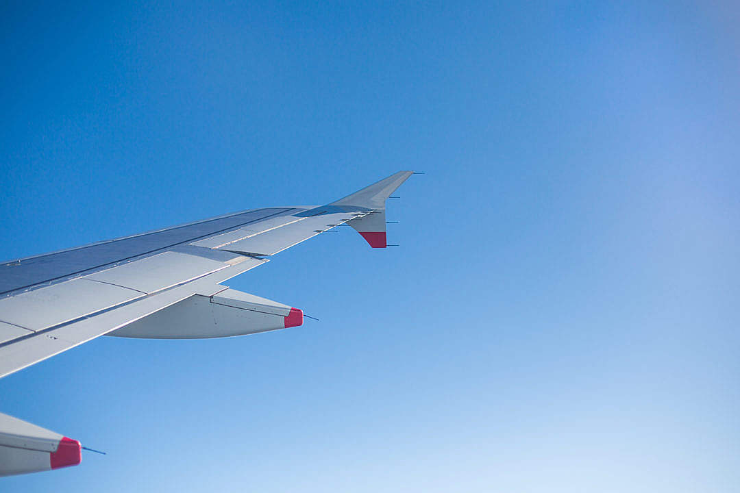 Download Airplane Wing and Bright Sky Through an Airplane Window FREE Stock Photo