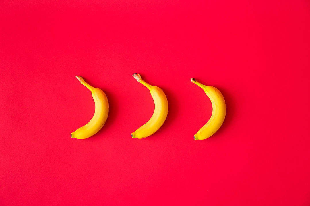 Download Bananas with Red Flat Background FREE Stock Photo
