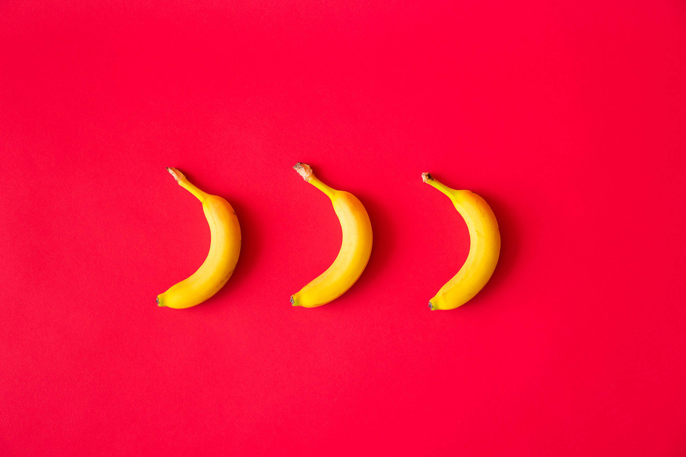 Bananas with Red Flat Background Free Stock Photo