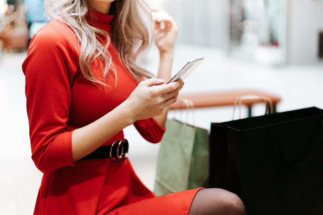 Download Beautiful Woman in Red Dress Using Her Smartphone FREE Stock Photo