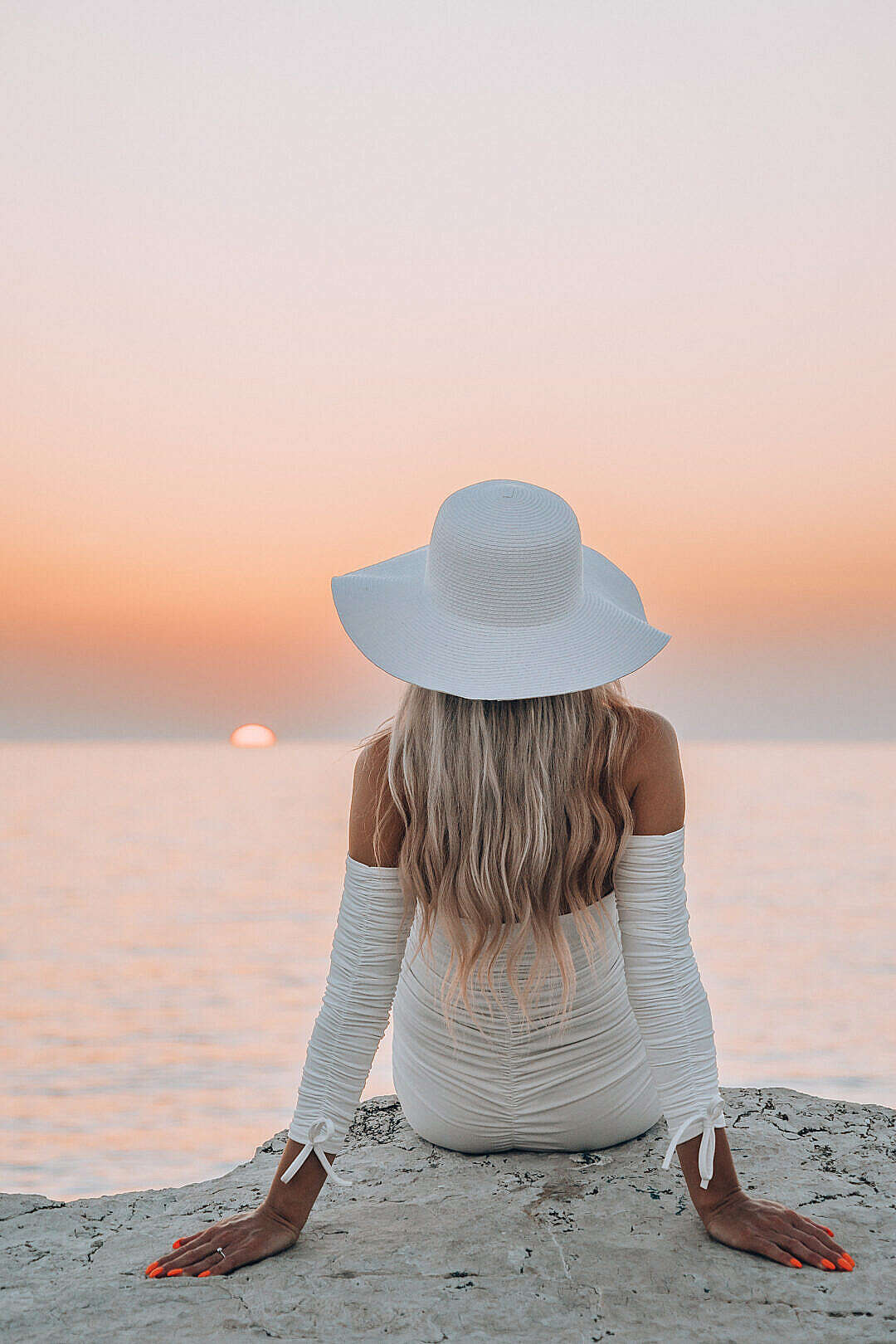 Download Beautiful Woman in White Hat Sitting on a Rock and Enjoying Sea Sunset FREE Stock Photo