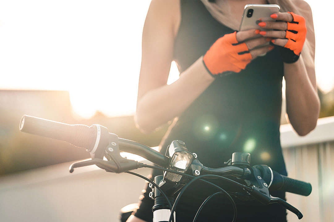 Download Bicycle Woman Planning a Cycling Route on Her Smartphone FREE Stock Photo