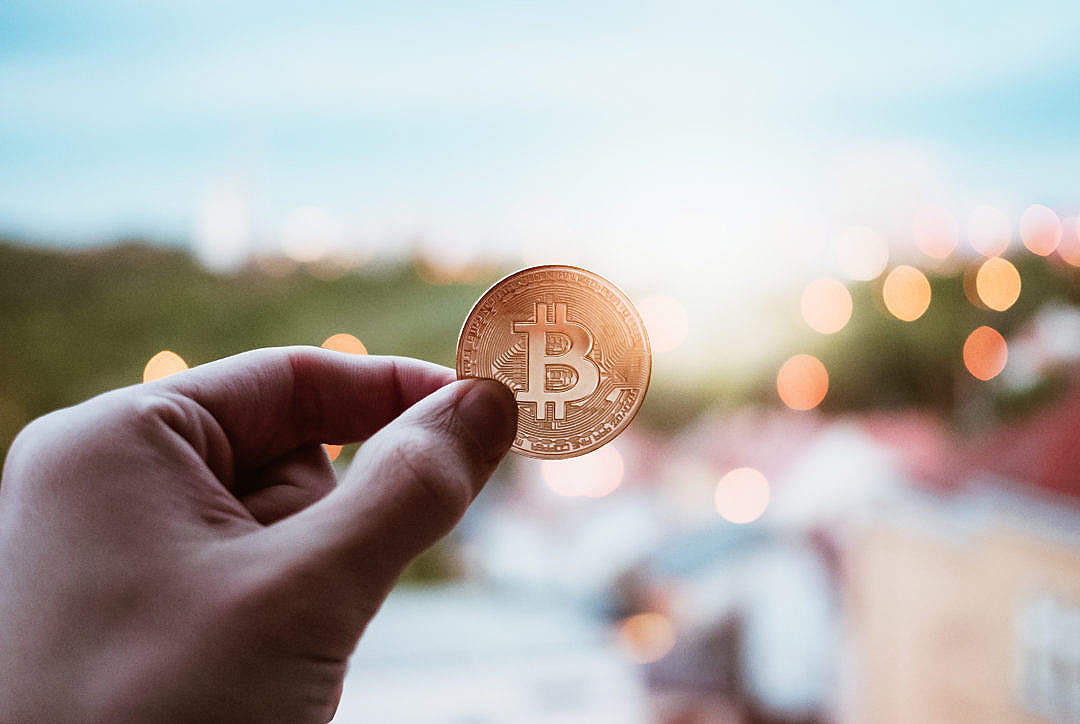 Download Bitcoin Coin Against an Evening City FREE Stock Photo