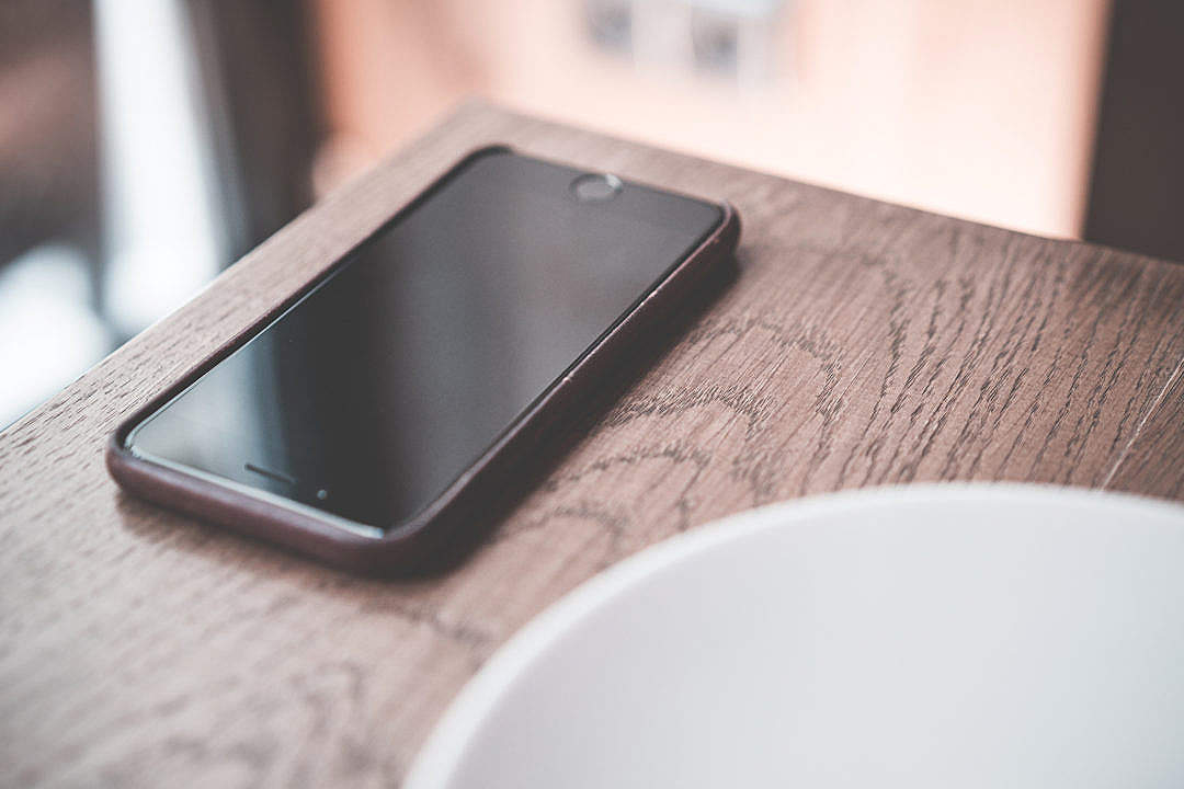 Download Black Smartphone on Wooden Table in Café FREE Stock Photo