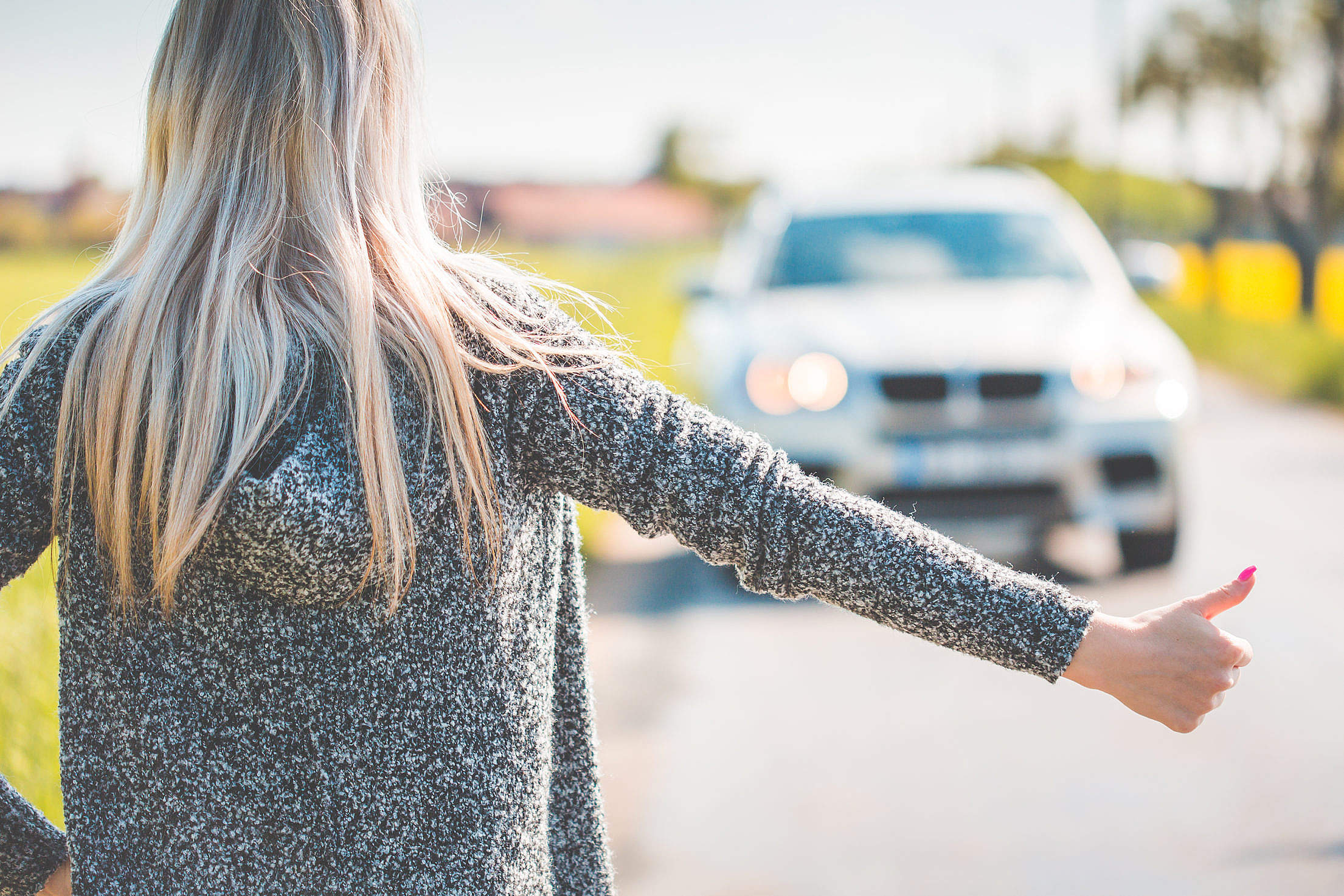 Blonde Woman Hitchhiking Because of Her Broken Car Free Stock Photo