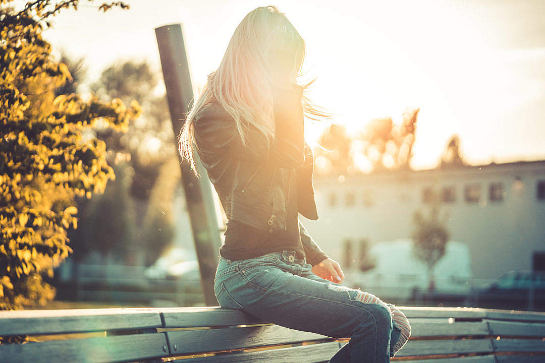 Download Blonde Woman Sitting Alone on a Bench Against Sunset FREE Stock Photo