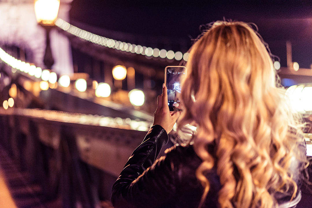 Download Blonde Woman Taking a Photo of an Old Bridge at Night FREE Stock Photo