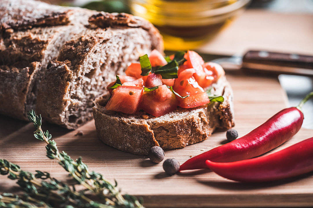 Download Bread with Tomatoes and Basil on The Chopping Board FREE Stock Photo