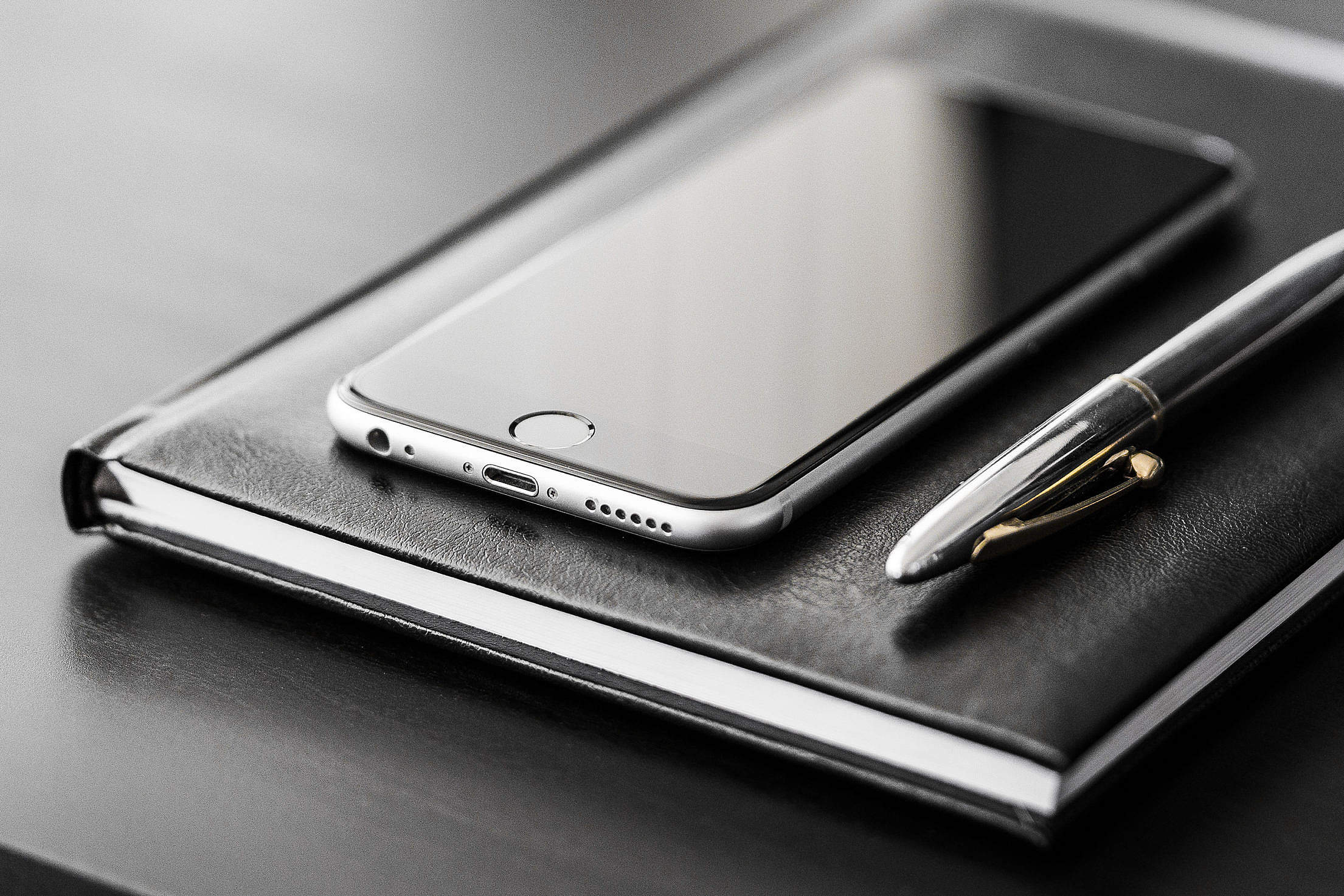 Business Gear: Smartphone, Silver Pen and Diary Free Stock Photo