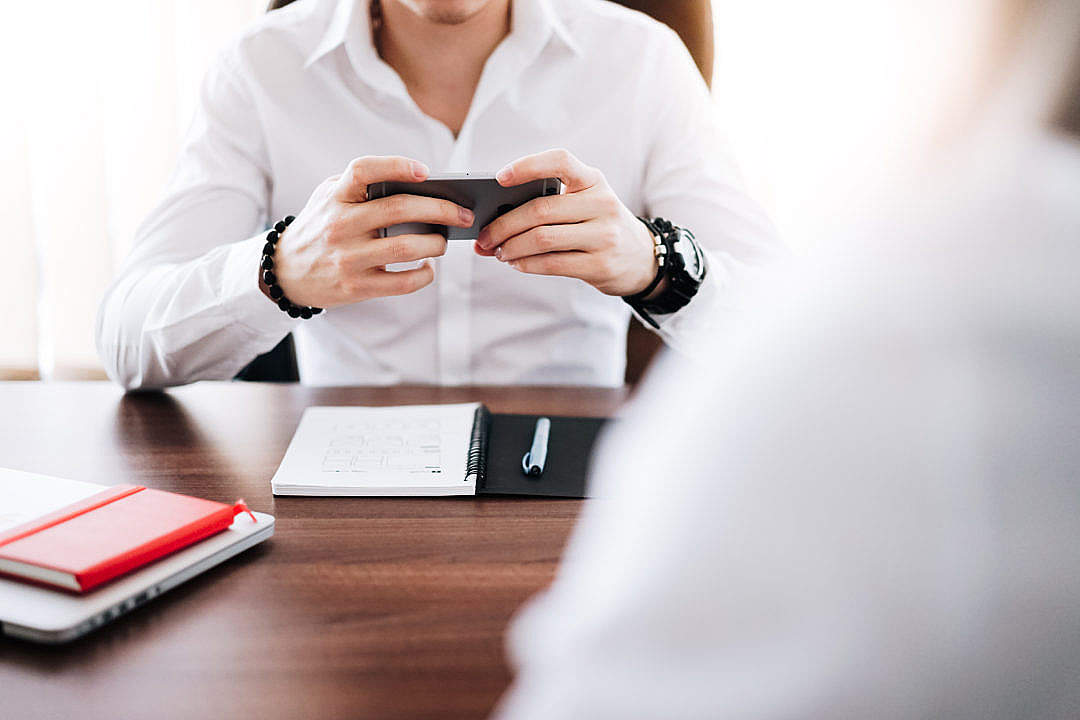 Download Business Man Working on His Smartphone in The Office FREE Stock Photo