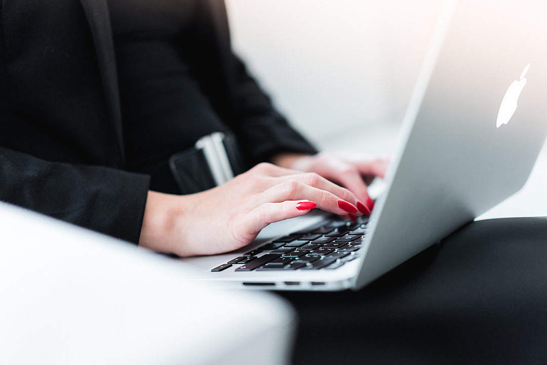Download Business Woman Typing on MacBook FREE Stock Photo