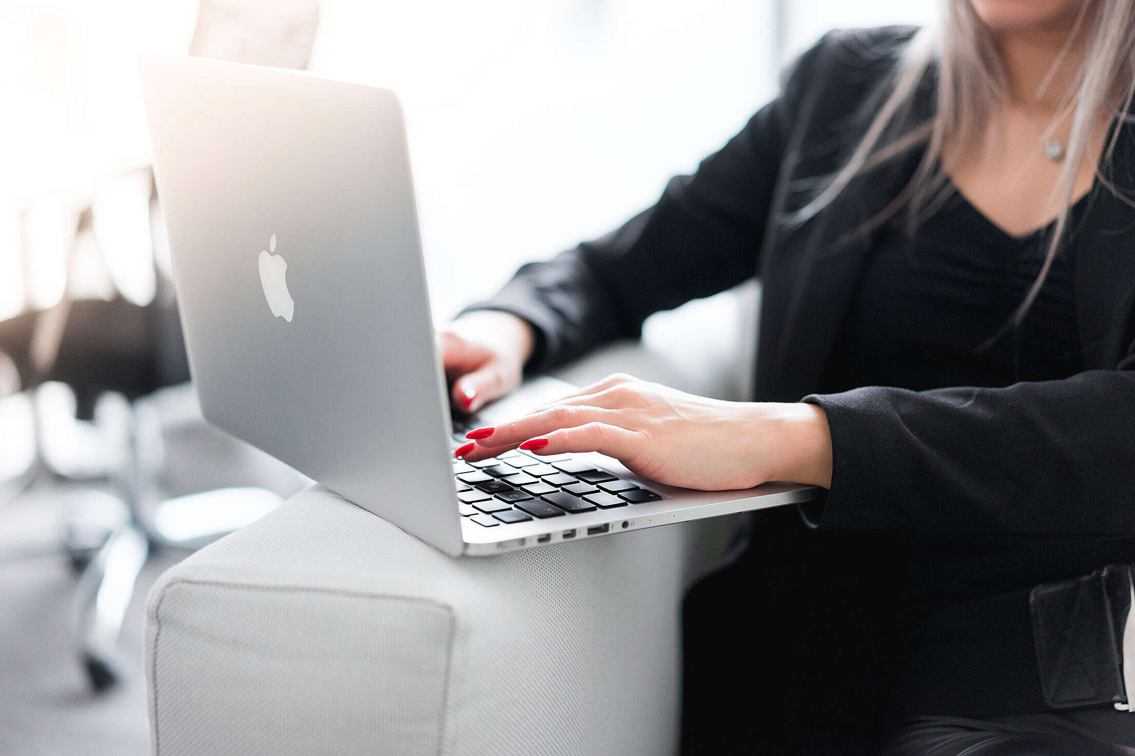 Business Woman Using Her Laptop on a Sofa Free Stock Photo