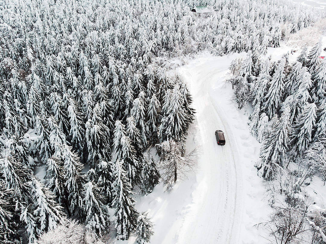 Download Car Driving on a Snowy Road in The Woods FREE Stock Photo