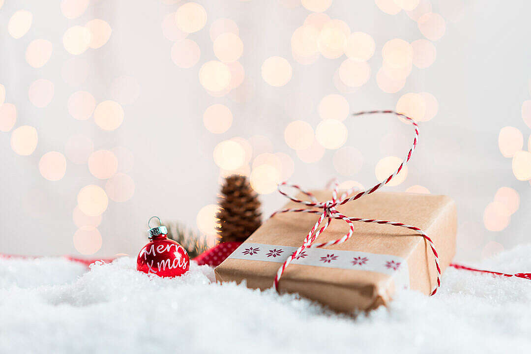 Download Christmas Present in Snow with Bokeh Background FREE Stock Photo