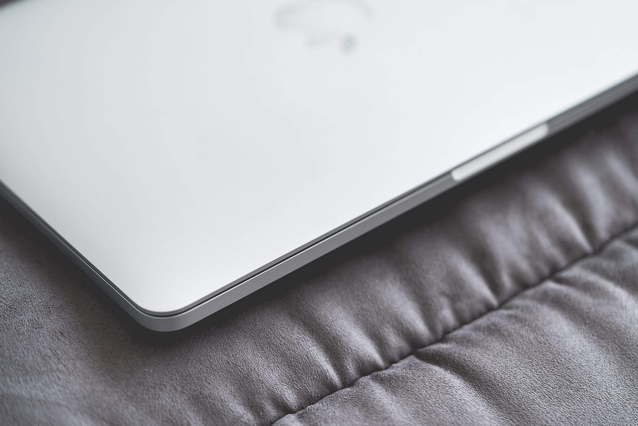 Closed Macbook Laptop on a Sofa #2 Free Stock Photo