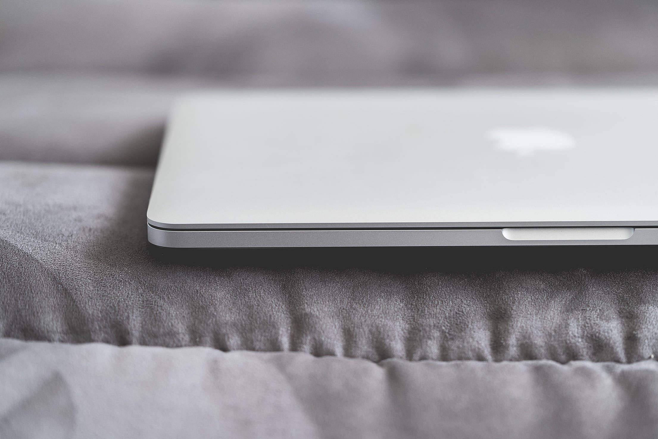 Closed Macbook Laptop on a Sofa Free Stock Photo