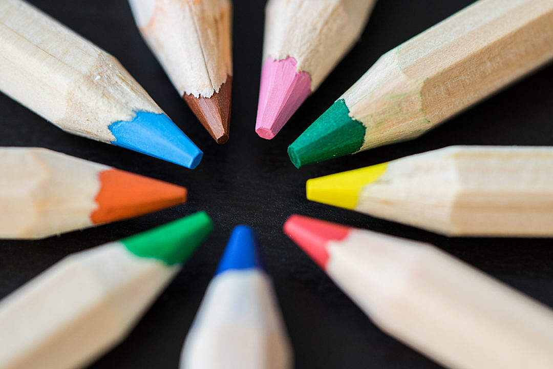 Download Colored Pencils in a Circle on a Black Desk FREE Stock Photo