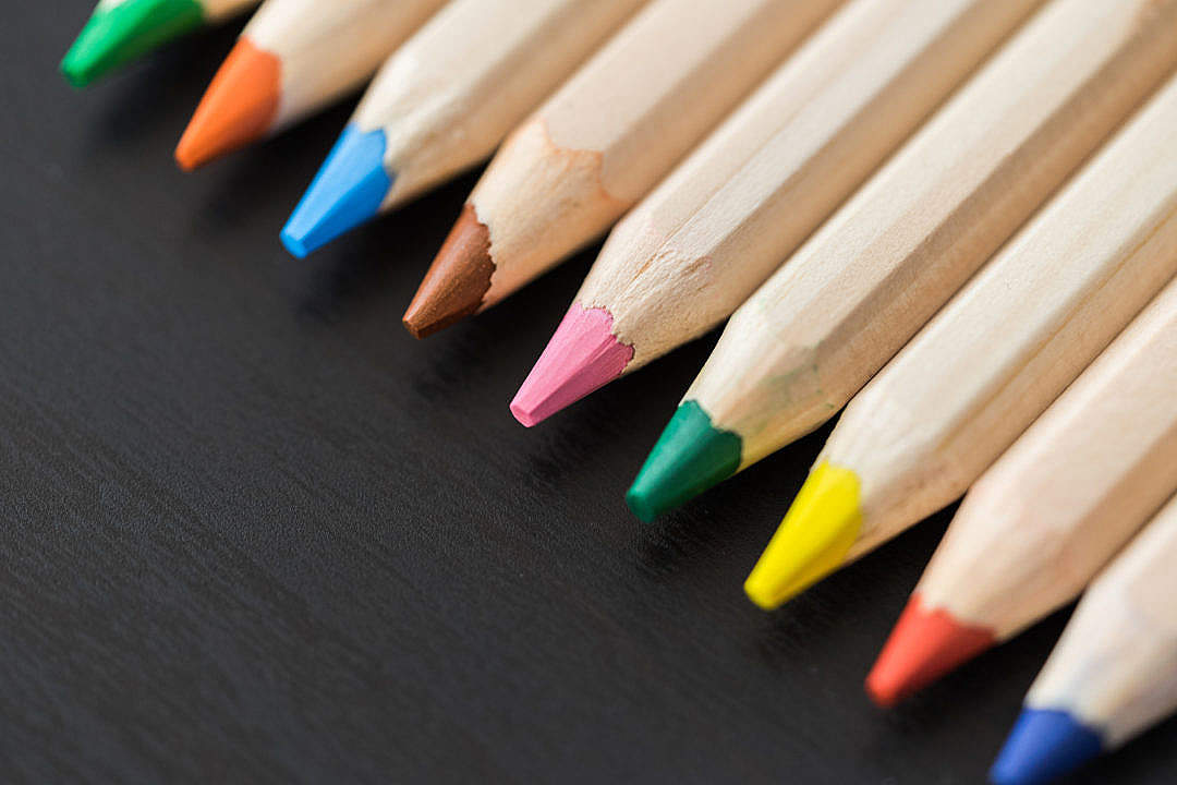 Download Colored Pencils in a Row on Black Desk Close Up FREE Stock Photo