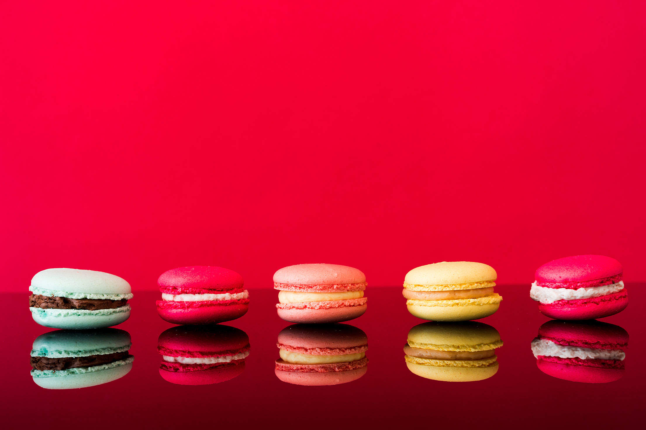 Colorful Yummy Macarons on Glossy Table and Red Background Free Stock Photo