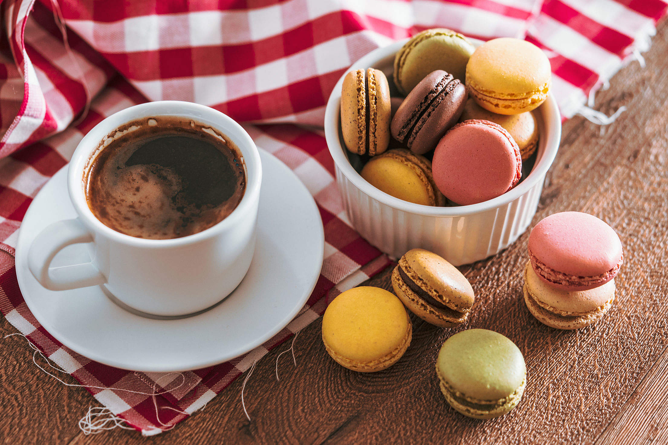 Colourful French Macarons with a Cup of Coffee on a Checked Cloth Free Stock Photo