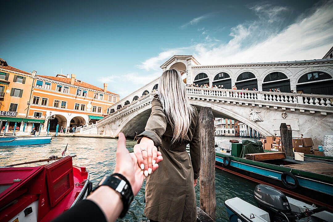 Download Couple in Follow Me To Pose in Front of Rialto Bridge, Venice FREE Stock Photo
