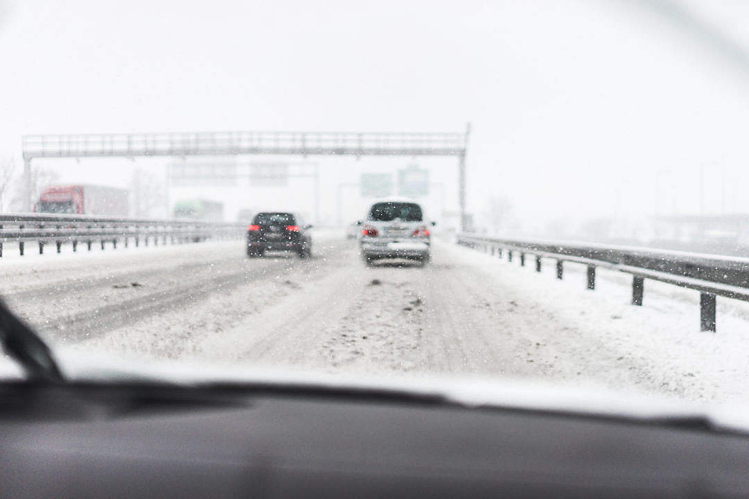 Download Driving in a Dangerous Snowy Weather on a Highway (focus on snowflakes) FREE Stock Photo