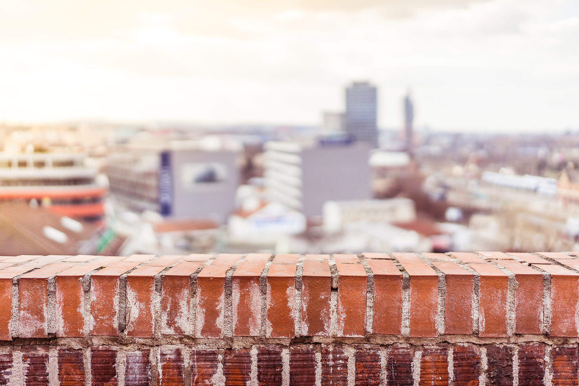 Empty Brick Wall with Blurred City View Background Free Stock Photo