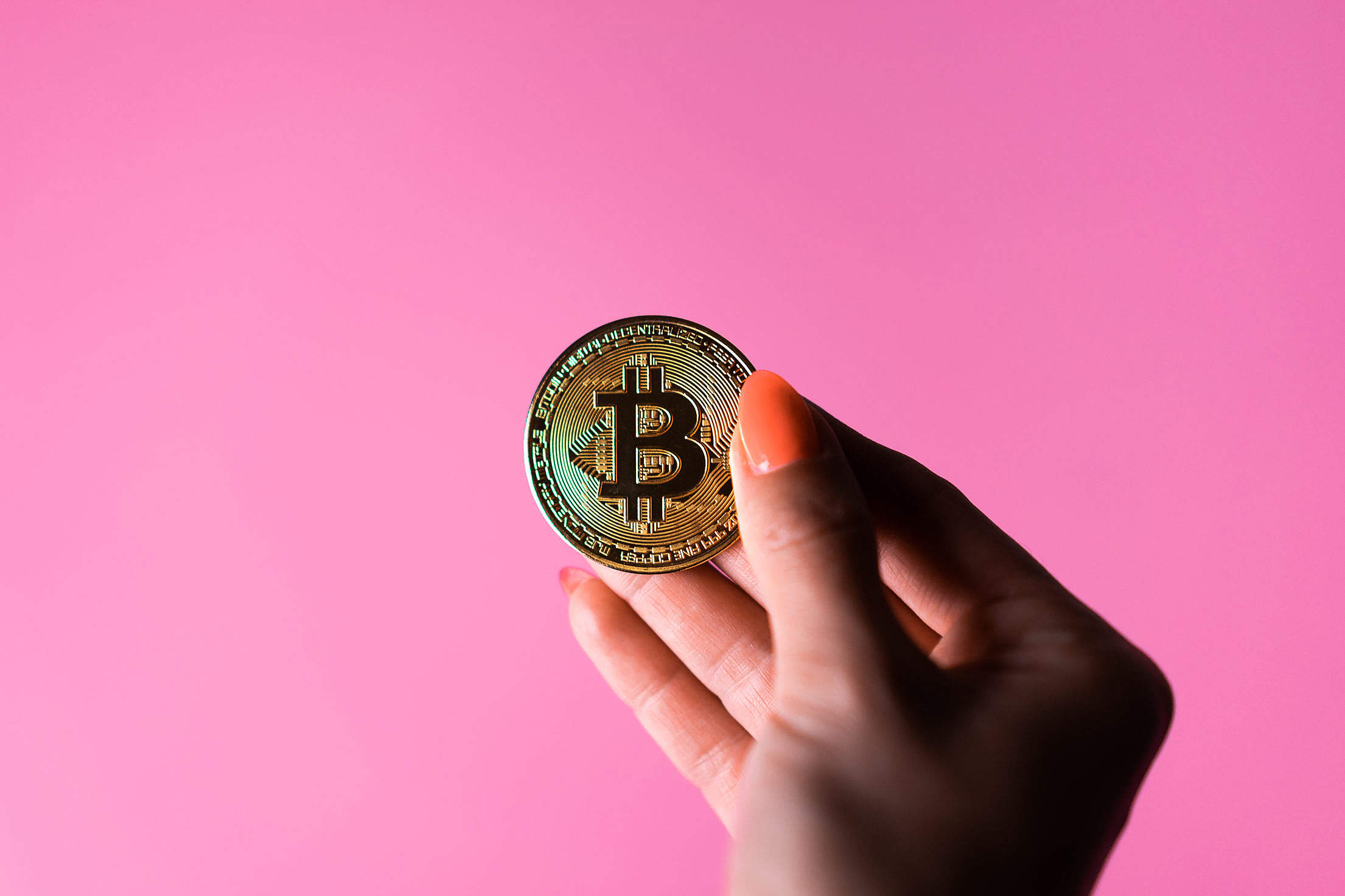 Female Hand Holding a Bitcoin on a Pink Background Free Stock Photo