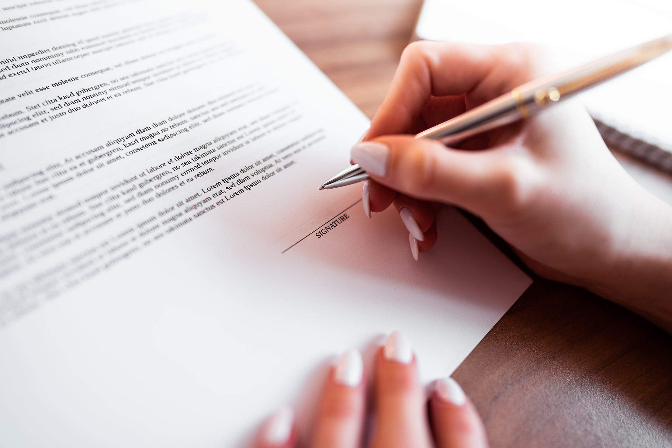 Female Hand Signing Insurance Contract Free Stock Photo