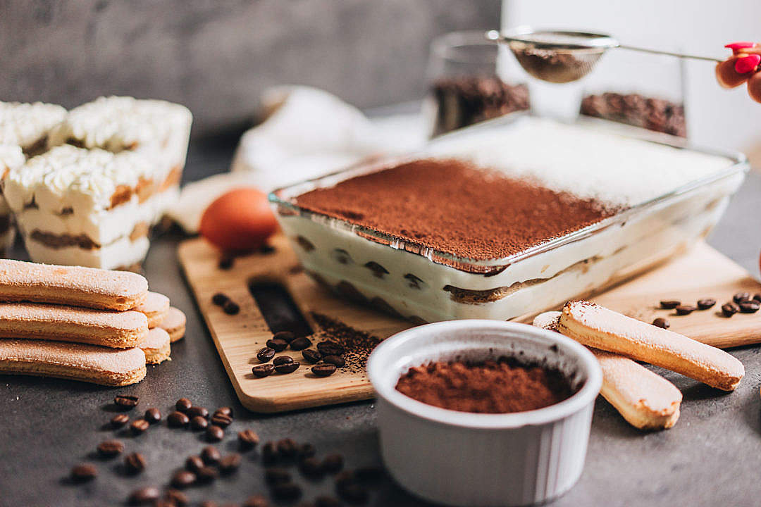 Download Female Hand Sprinkling Cocoa Powder on Tiramisu FREE Stock Photo