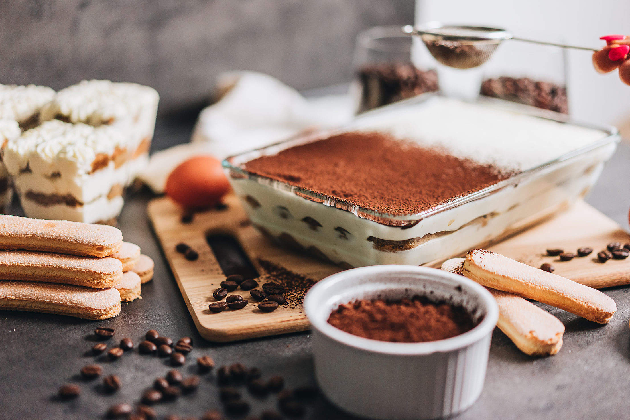 Female Hand Sprinkling Cocoa Powder on Tiramisu Free Stock Photo