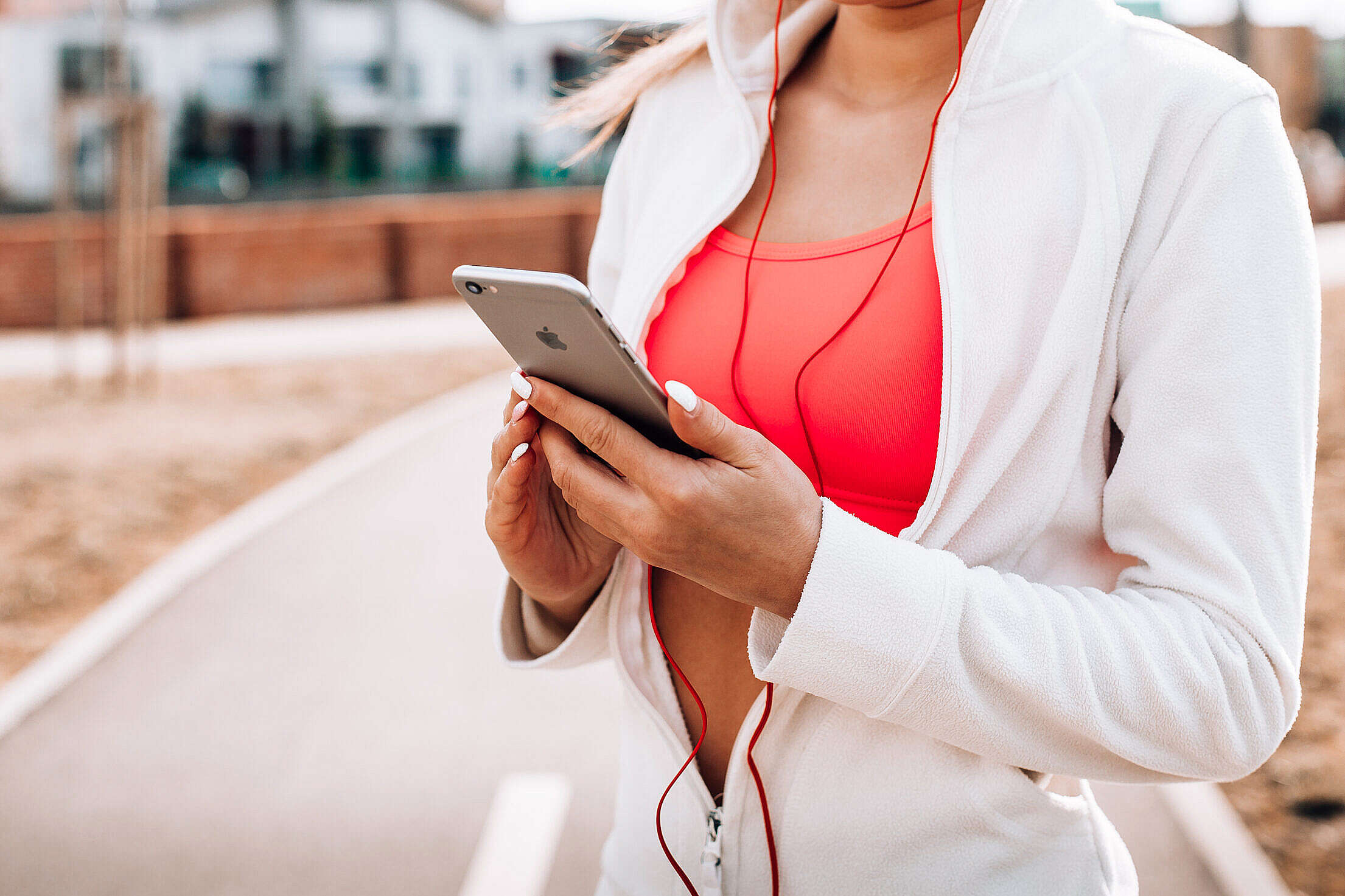 Fit Girl Listening to Music on Her iPhone Free Stock Photo