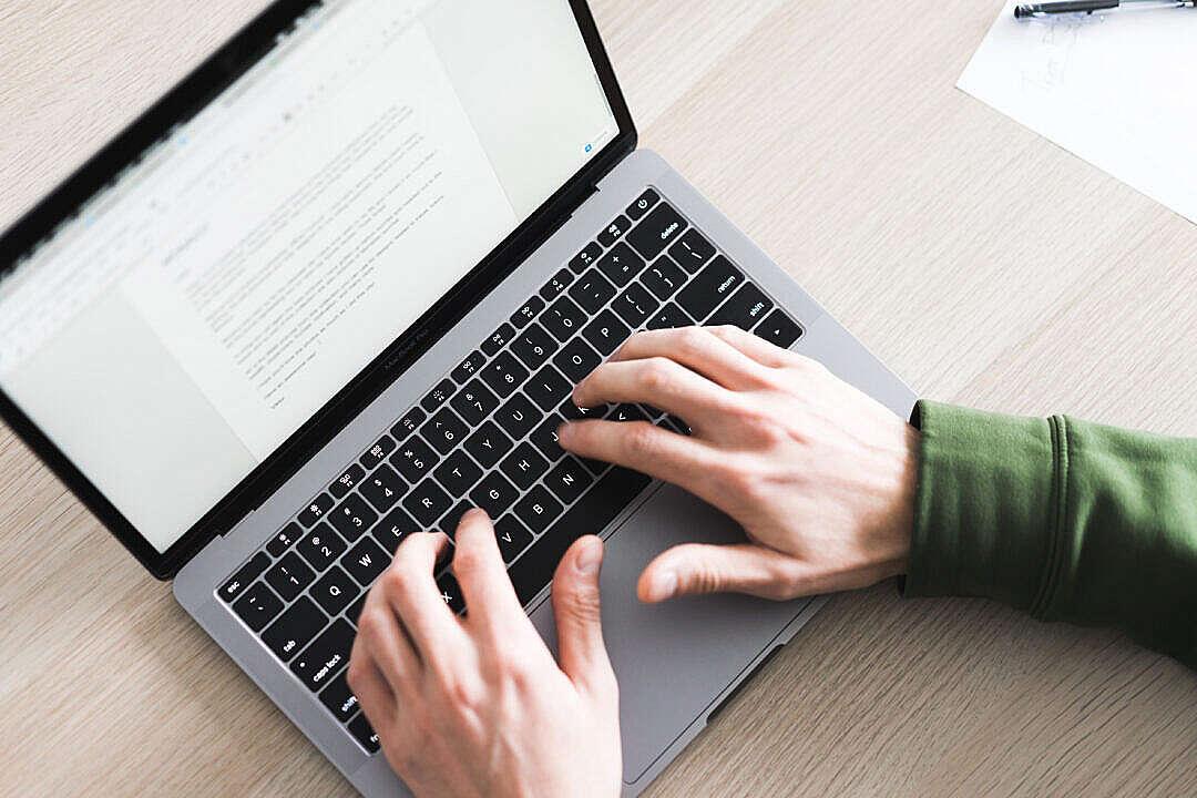 Download Freelance Copywriter Working on His Silver Laptop FREE Stock Photo