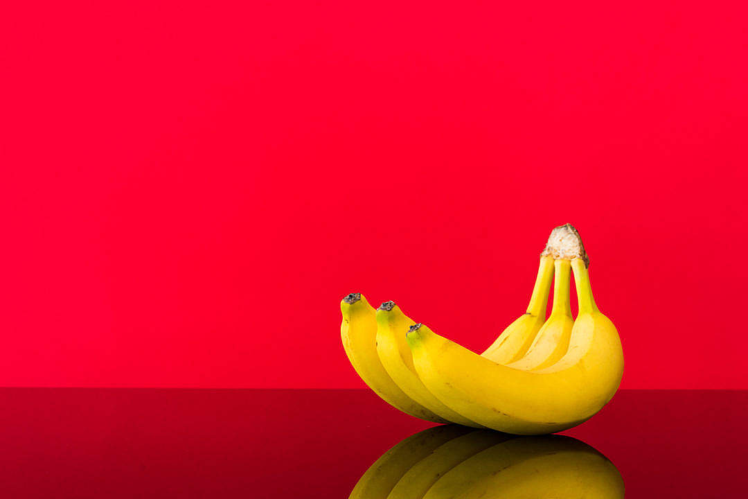 Download Fresh Bananas on Glossy Table and Red Background FREE Stock Photo