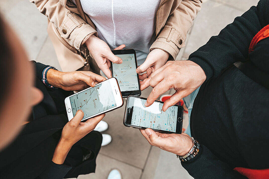 Download Friends Using Their Smartphones to Find The Right Way FREE Stock Photo