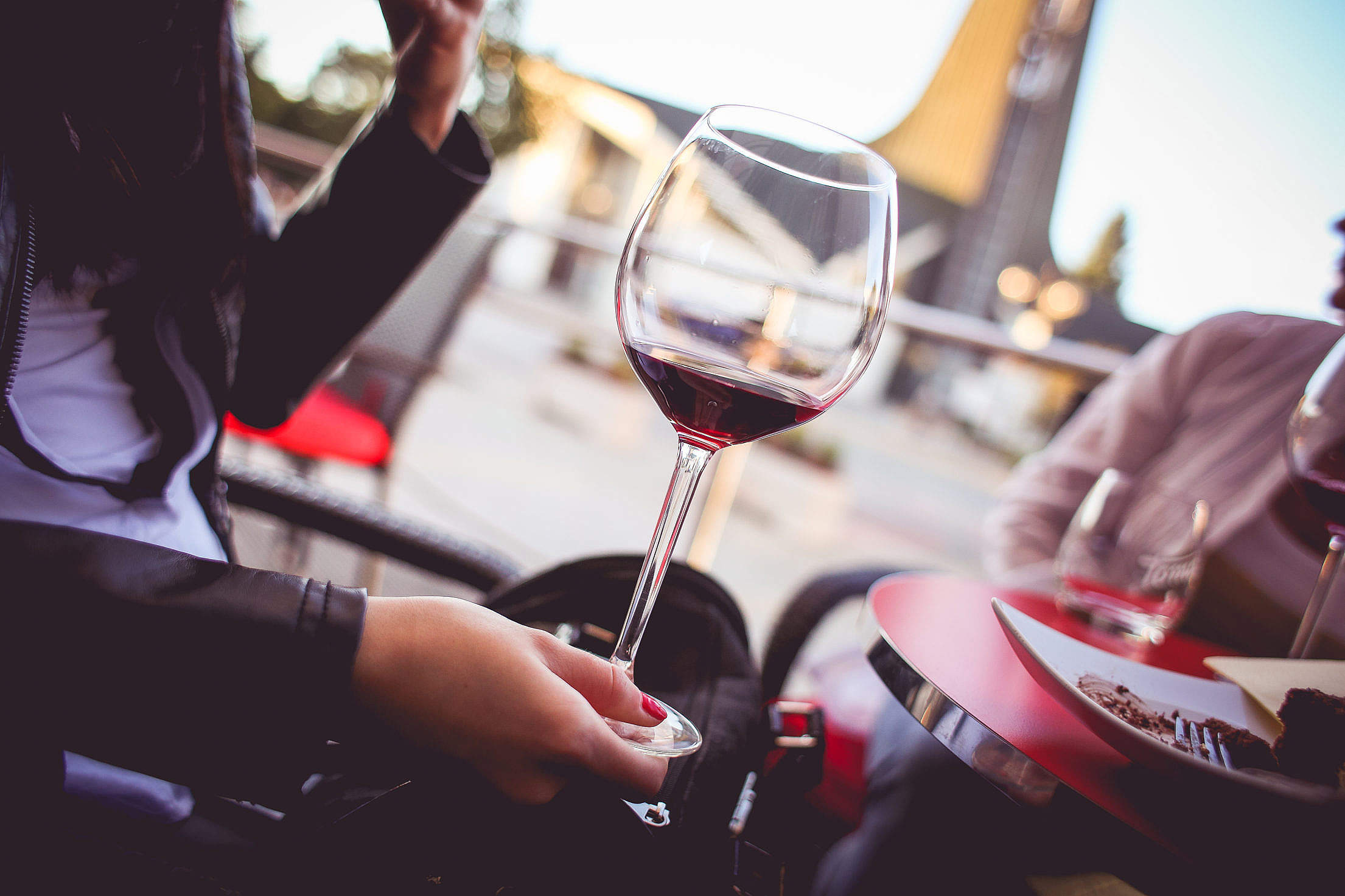 Girl Holding a Glass with Red Wine Free Stock Photo