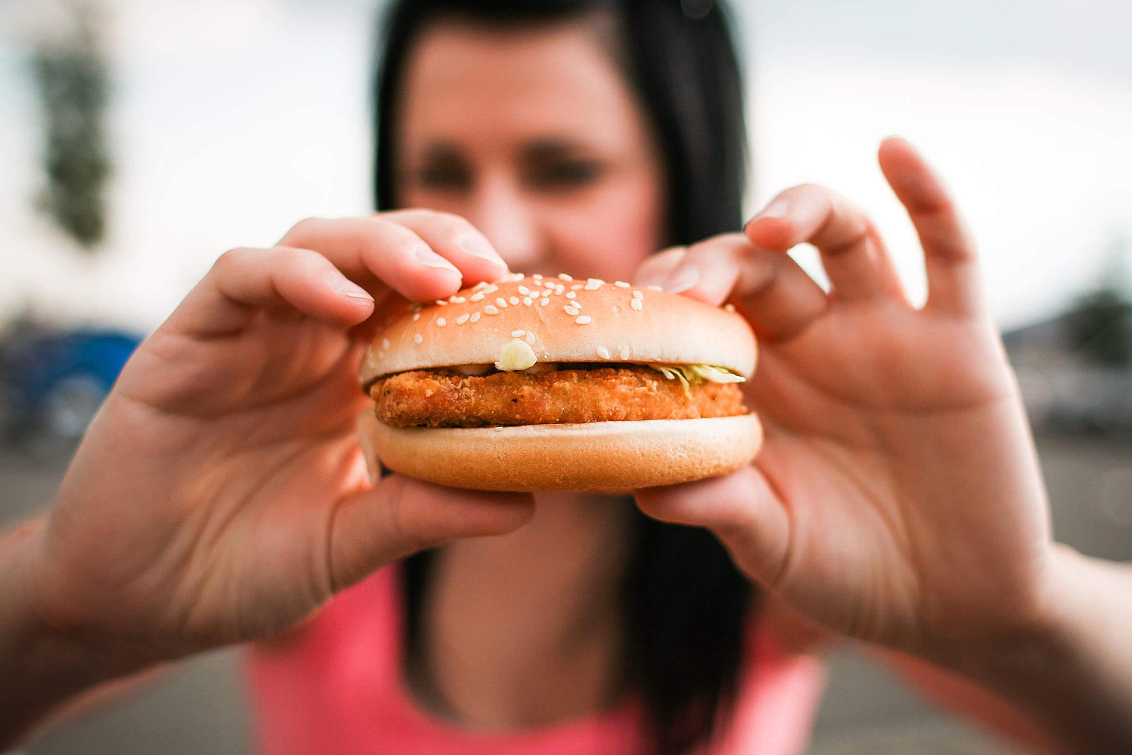 Girl holding Hamburger in her Hands Free Stock Photo