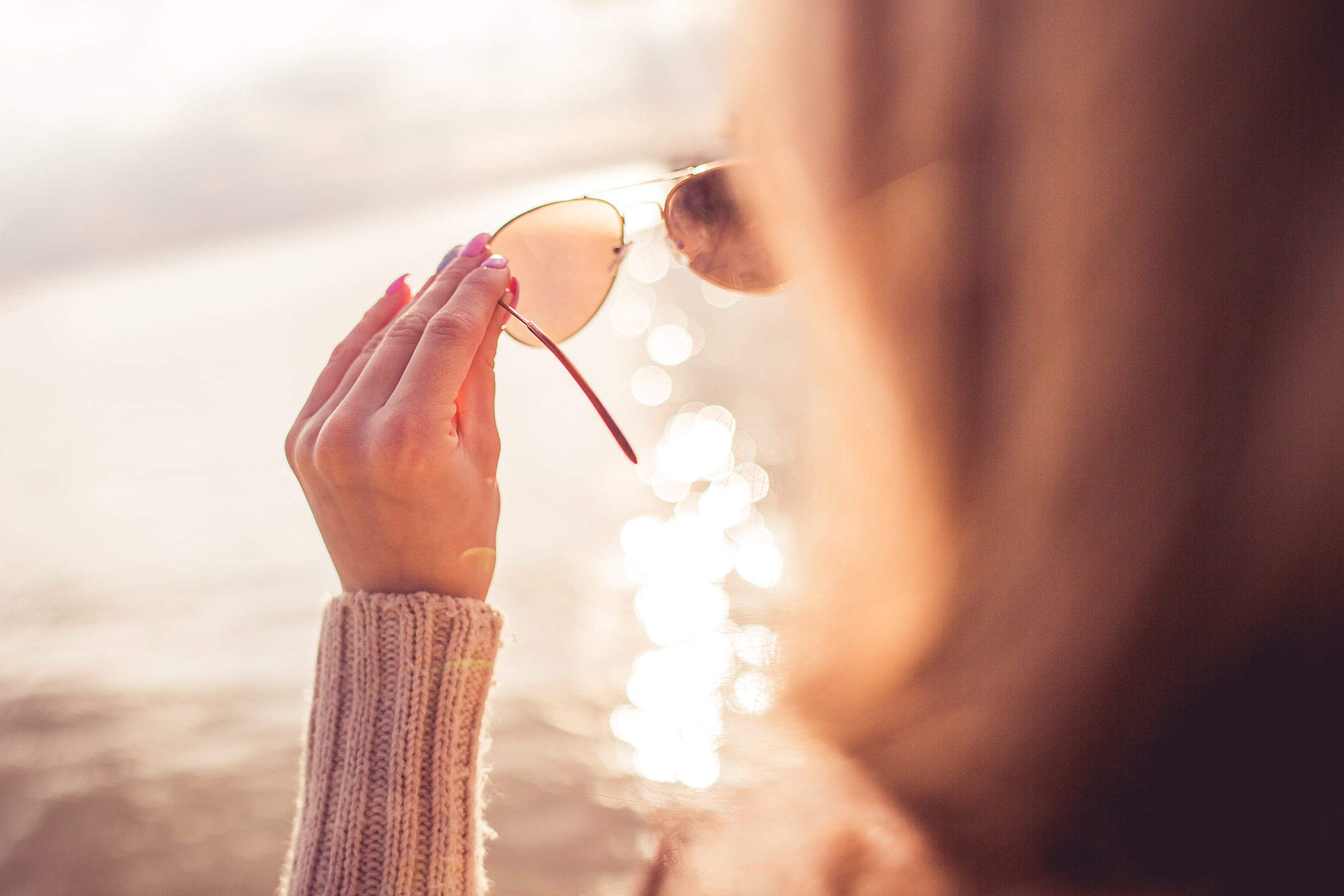 Girl Looking at the Sea Through Sunglasses Free Stock Photo