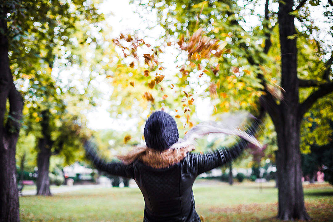 Download Girl Throwing Autumn Leaves in The Air FREE Stock Photo