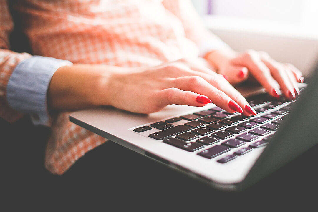 Download Girl Typing on her MacBook Pro Close Up FREE Stock Photo