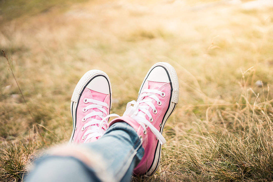 Download Girl With Pink Shoes Laying in Meadow FREE Stock Photo