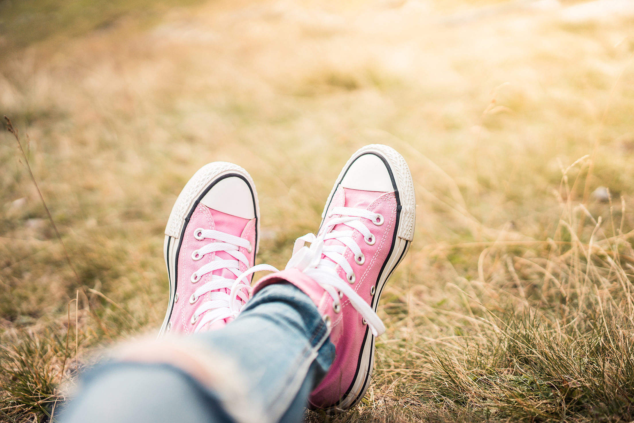 Girl With Pink Shoes Laying in Meadow Free Stock Photo
