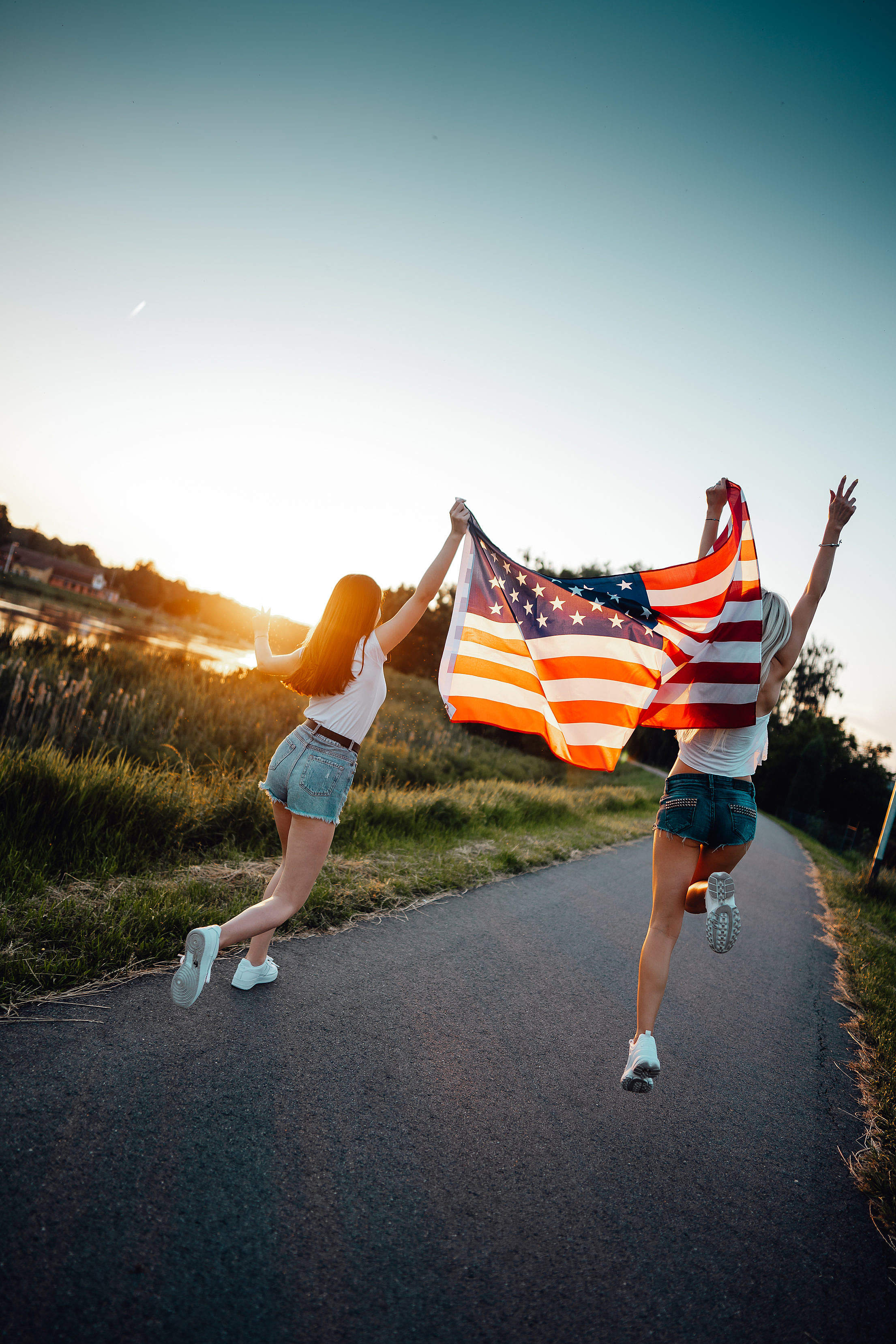 Girls Dancing with an American Flag Free Stock Photo
