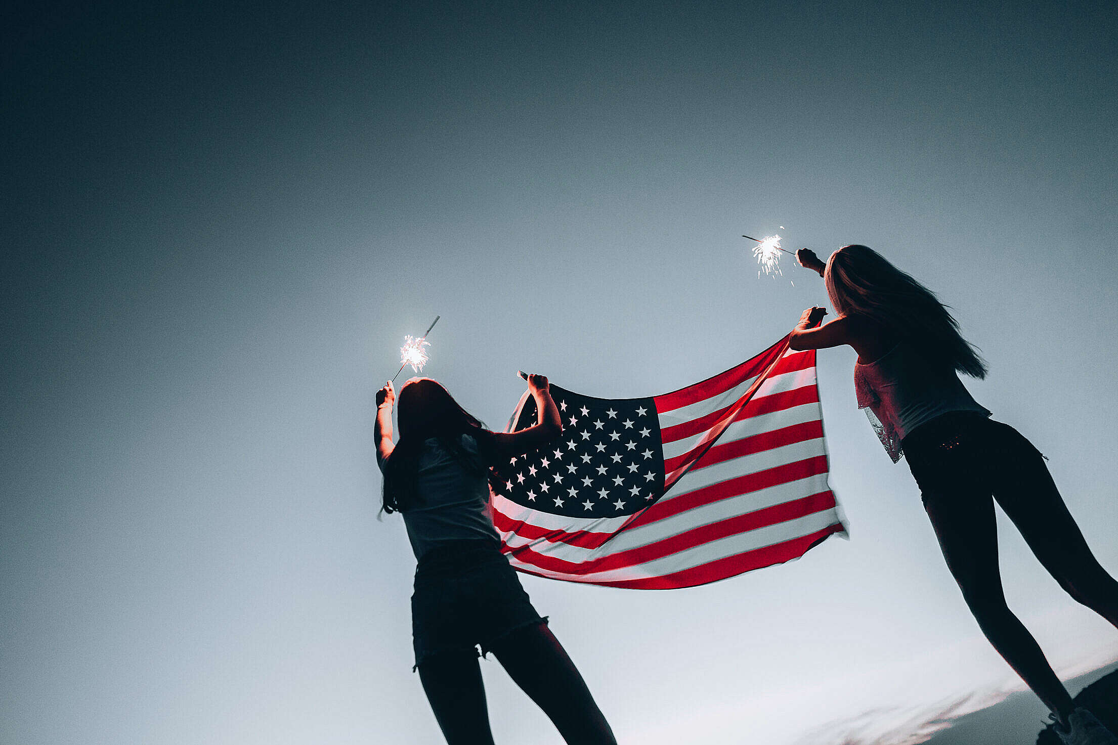 Girls Holding American Flag and Sparklers Free Stock Photo