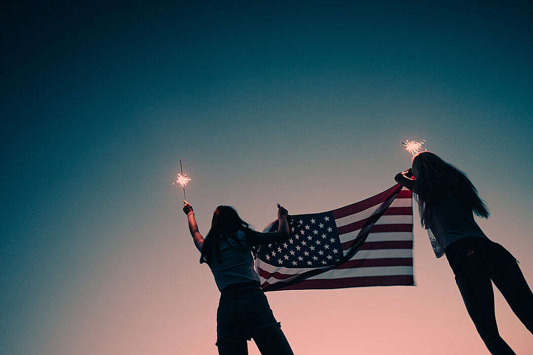 Download Girls Holding American Flag and Sparklers in The Early Evening FREE Stock Photo