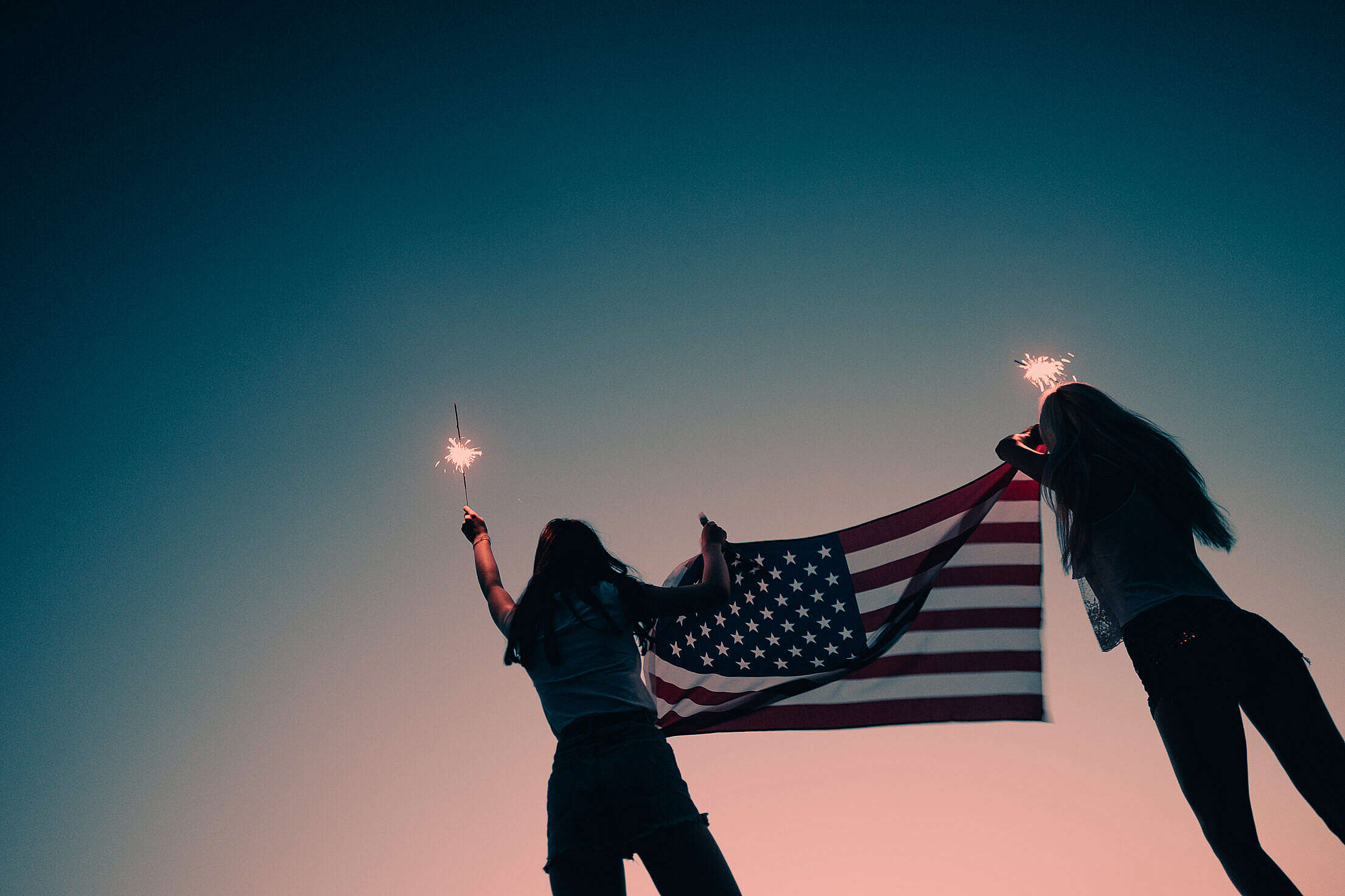 Girls Holding American Flag and Sparklers in The Early Evening Free Stock Photo