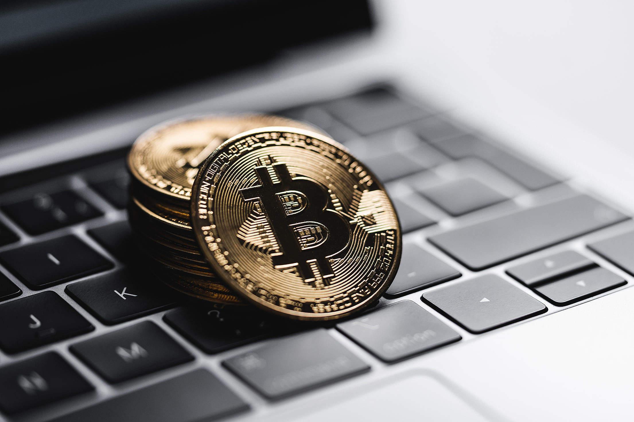 Gold Bitcoin Coins on Laptop Keyboard Free Stock Photo